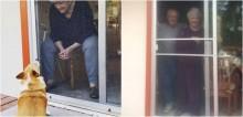 Morrendo de vontade de ganhar abraço de avó, cadela corgi a vê sempre pela janela de vidro em meio a quarentena