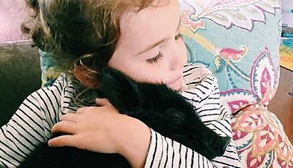 A menina Phoenix Parke abraçada com o leitão.
