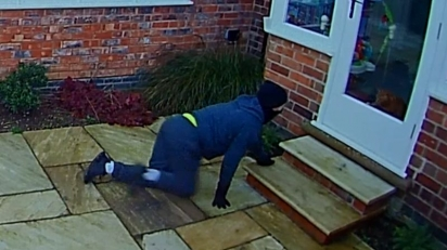 Ladrão de aproxima da casa e gato permanece a observá-lo pelo vidro da porta. (Foto: Reprodução Facebook/Nottinghamshire Police)