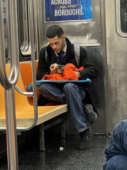 Homem sentado em banco no metrô alimentando gatinho que resgatou das ruas de Nova York. (Foto: Facebook/Gillian Rogers)