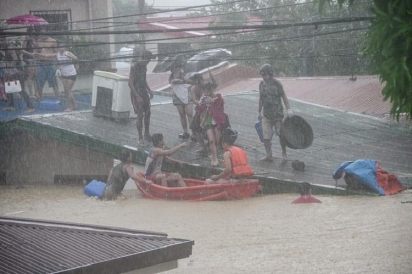 Voluntários de resgate evacuam residentes enquanto as águas da enchente submergem casas em Filipinas. (Foto: Facebook/Larry Monserate Piojo)