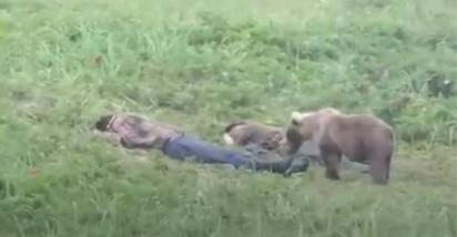 O jovem urso se aproxima dos homens para cheirá-los. (Foto: Reprodução Youtube/ViralOne)