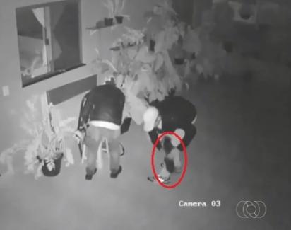 Um dos ladrões se agacha para pegar o cachorro de pequeno porte no colo. (Foto: Divulgação/Polícia Militar)