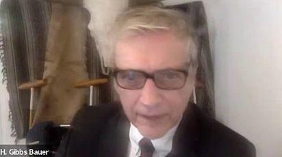 O advogado H. Gibbs Bauer coloca o óculos e olha o monitor para confirmar a situação hilária.