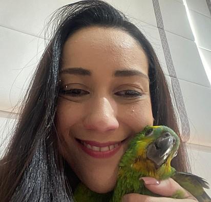 A empresária Christiane Teixeira e seu papagaio, Mefi.