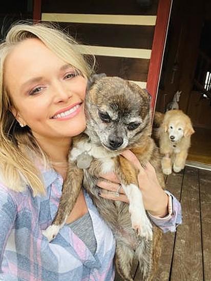 Miranda com seus dois cães adotados, Delta e Jessi.