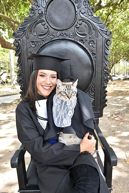 O gato Tigrão, de 10 anos, comemorando a sua formatura com a dona, Tainá Brilhante.