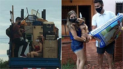 O casal foi fotografado se mudando com o seu cachorrinho nos braços.
