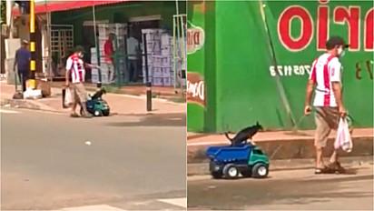 Homem carrega seu cachorro em caçamba de caminhão de brinquedo.
