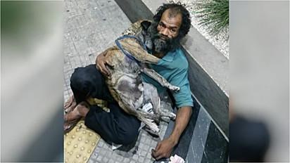 Mulher vê doce cena de morador de rua abraçando o seu cachorrinho em São Paulo.
