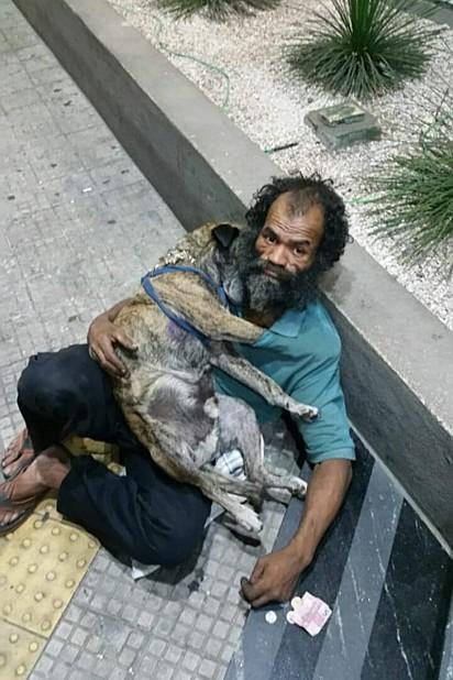 Morador abraça sua única família: o cão.