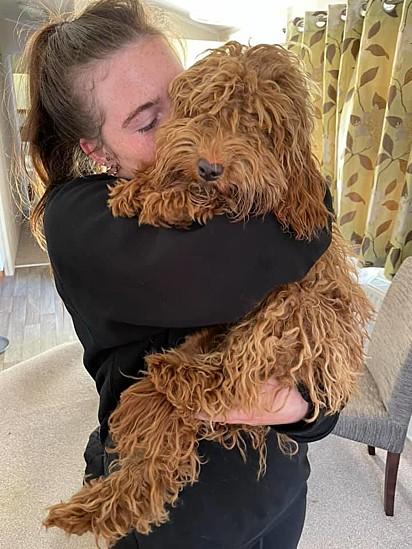 Sophie May Dell abraça fortemente a cadelinha Blossom.