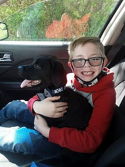 Bryson Kliemann segura no colo o seu cachorrinho.