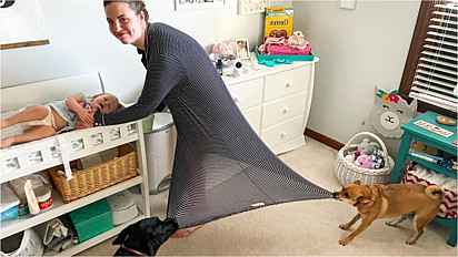 Mulher é registrada em foto que caracteriza a vida de uma mãe com filho e pets.