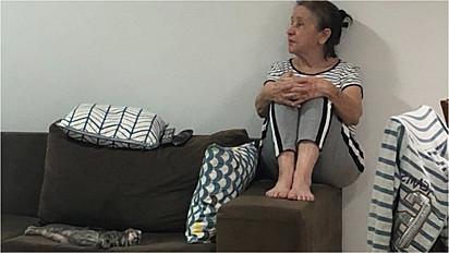 Idosa é flagrada sentada no braço do sofá para ceder o assento para o gatinho.