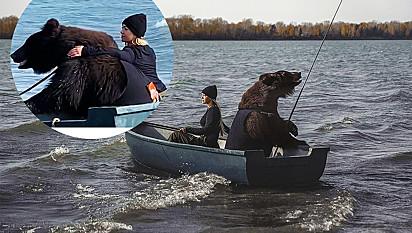 Urso pesca com mulher em barco.