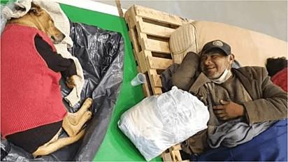 Idoso sorri para o seu cachorro após serem acolhidos em abrigo para se protegerem do frio.