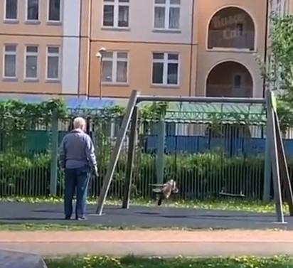 O idoso foi flagrado brincando com o seu gato no parque.