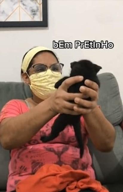 A mãe está olhando para a gatinha enquanto segura em suas mãos