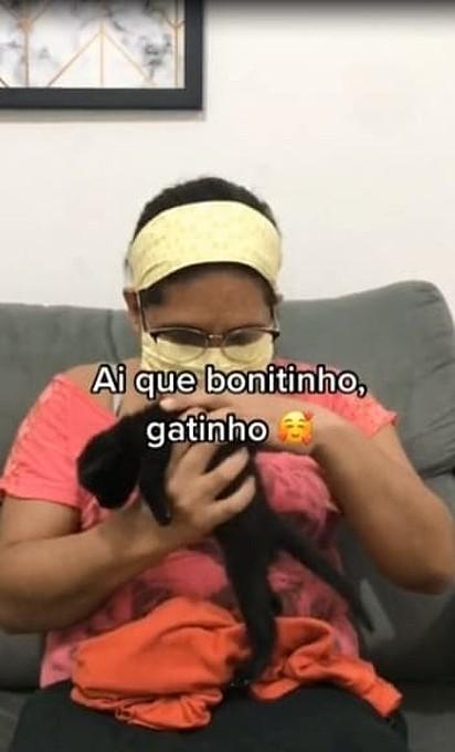 A mulher está segurando o gatinho
